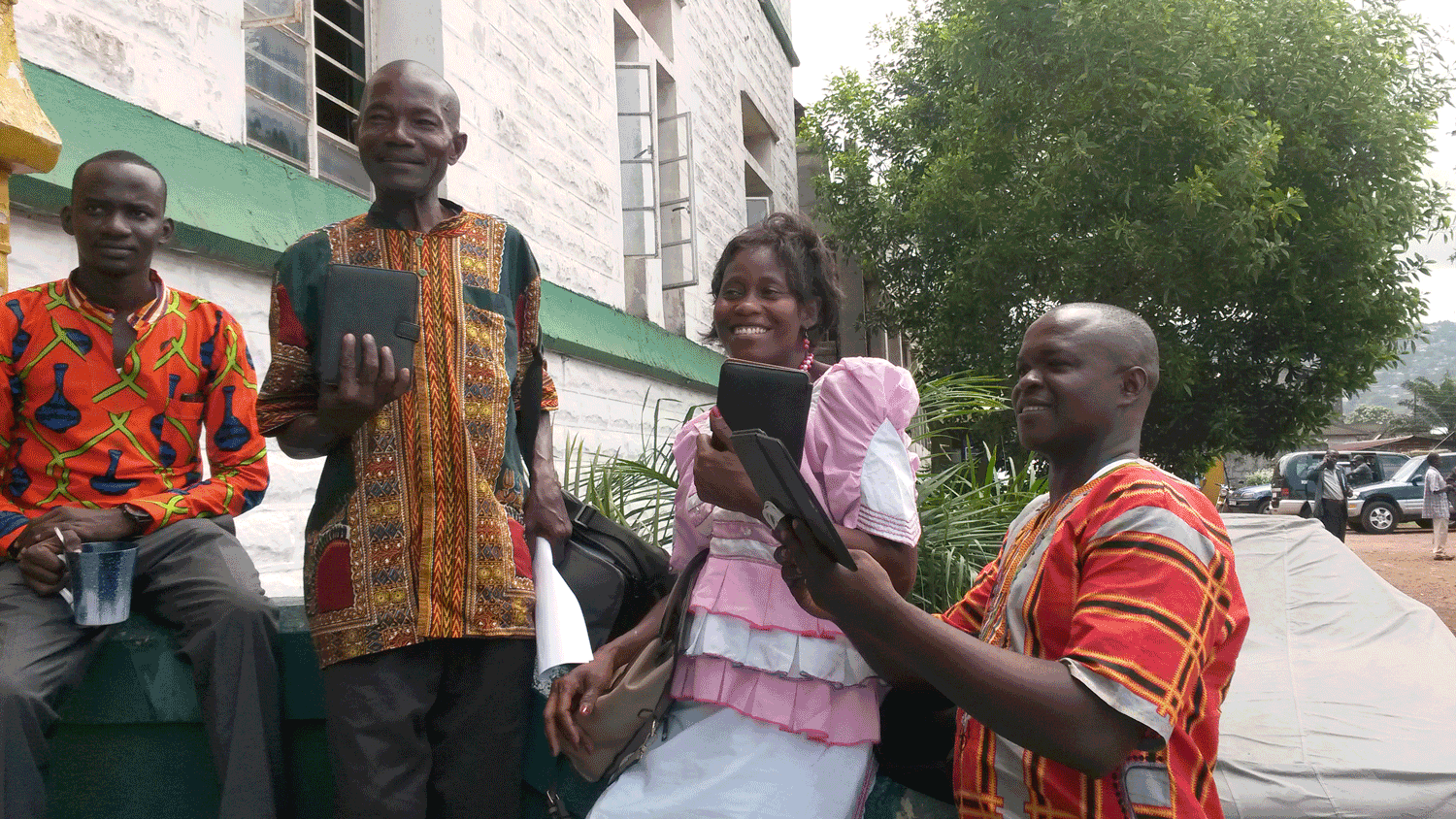 Vicctor Kallon, Anthonette Singbeh, and Patrick Vandi pose with their e-readers