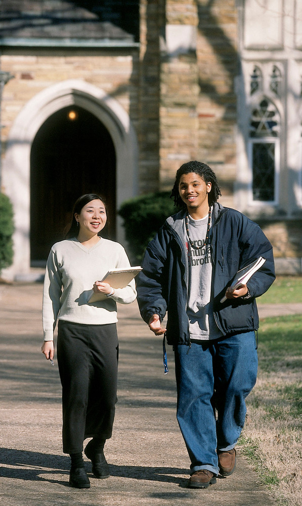 Two students holding notebooks walking together.