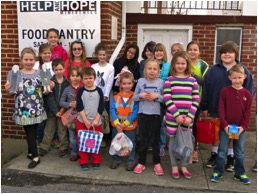 Children of Mountain View UMC in Kingsport, TN, bring groceries and Flat Wesleys to a local food pantry. The girl in the front row, far left, holds up the Flat Charles and Flat John Wesley.