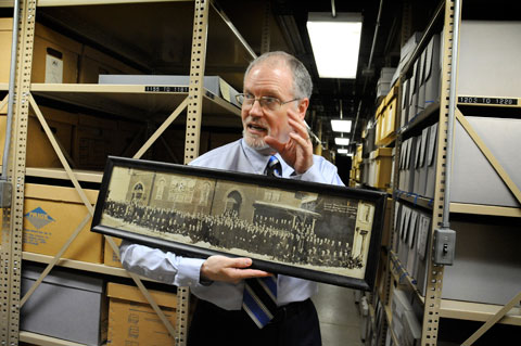 Man holding antique photo in the UMC Archives and History Center